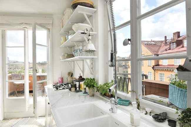 Las ventanas de vidrio repartido potencian la luminosidad de la cocina blanca