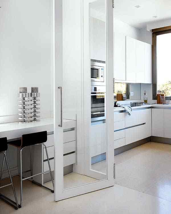 Una puerta vidriada de gran tamaño permite separar el área del comedor diario del de la cocina sin interrumpir el flujo de luz natural