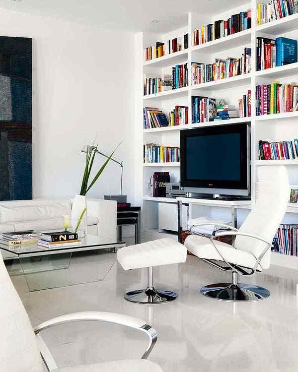 Casa con interiores modernos contemporáneos: living en blanco con acentos de color aportados por los libros y los cuadros