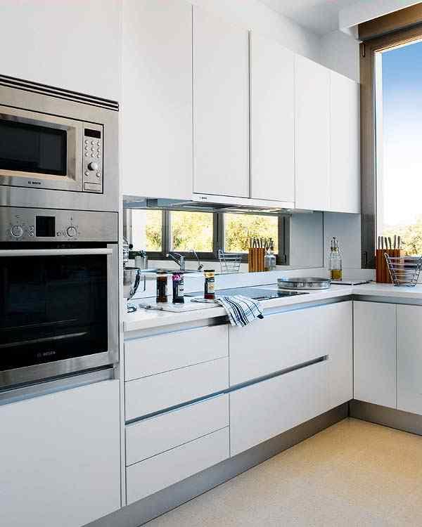 Casa con interiores modernos contemporáneos: cocina funcional con muebles blancos y mesada de silestone