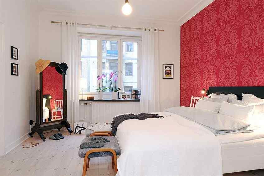La pared principal del dormitorio se revistió con papel rojo con motivos
