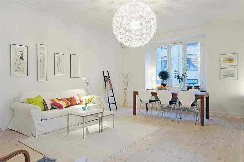 Living comedor en un mismo ambiente pintado de blanco con pisos de madera clara