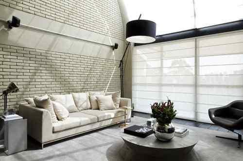 Living doble altura en loft de estilo industrial