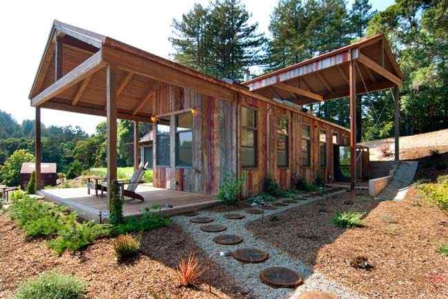 Exterior de la casa con revestimientos de maderas recuperadas / recicladas