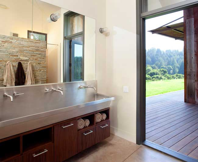 El baño con la pared de la ducha revestida en piedra y un mueble vanitory en acero y madera