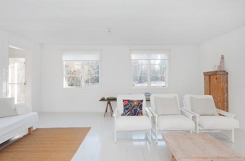 Living blanco en cabaña minimalista