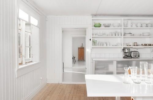 Cocina blanca minimalista en cabaña