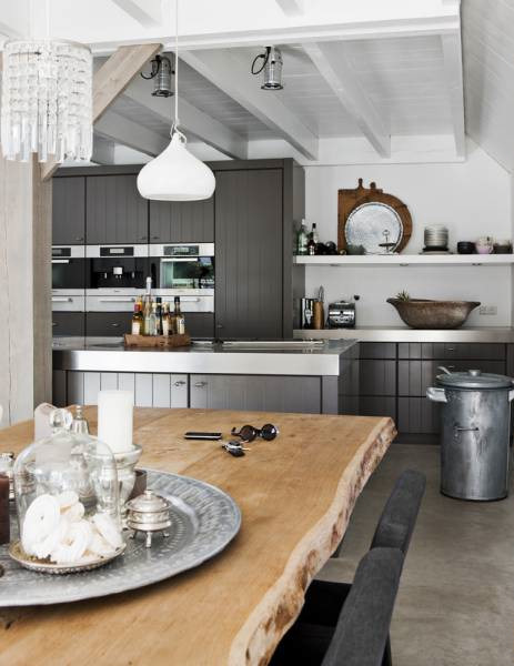 Comedor y cocina en estilo rústico moderno con pisos de cemento alisado