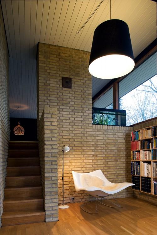 Biblioteca en un desnivel con un sillon de diseño
