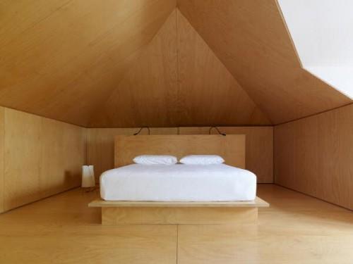 Dormitorio con panelado de madera clara y cama moderna