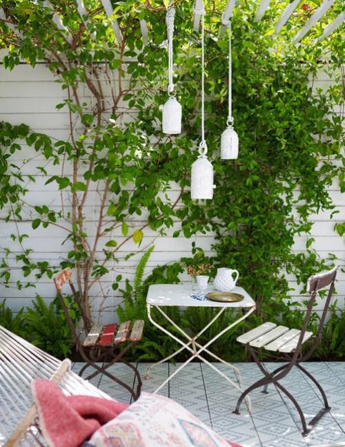 Jardín con mesita y sillas clásicas de exterior