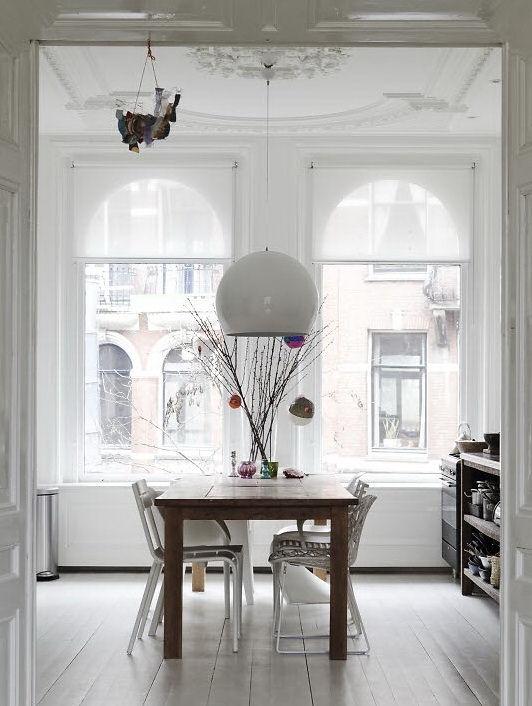 No había espacio para un área de comedor y por eso se armó en la cocina con una mesa de madera rústica y sillas de diferentes estilos en blanco