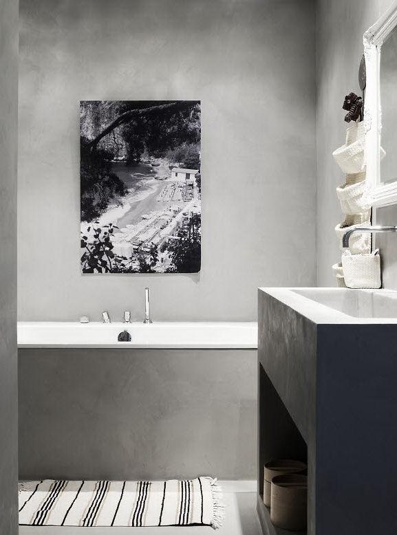 Baño con paredes y pisos revestidos en cemento alisado al igual que el mueble vanitory