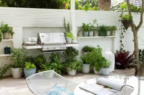 Jardin moderno con parrilla y macetas con plantas aromaticas