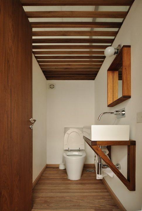 Toilette con pisos de madera, soporte para la bacha y espejo también en madera. En lugar de cerrar el techo, se colocaron listones con vidrio como terminación para aprovechar mejor la luz natural del ambiente