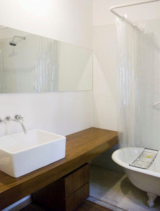 Baño principal del PH al que se accede sólo desde el dormitorio. Las paredes revestidas en venecitas blancas, el mueble en madera y la bacha apoyada dan al baño un estilo muy actual