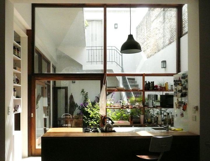 La cocina del PH se integra al ambiente con una mesada que también sirve de barra. Los grandes ventanales extienden la vista hacia el patio interno.