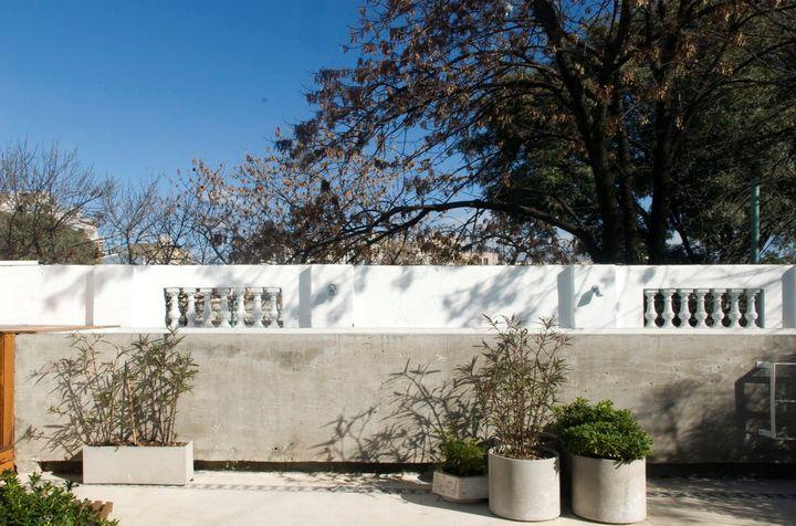 Desde otro ángulo de la terraza, la pileta pasa casi inadvertida gracias a la terminación en cemento que la asemeja mucho a un cantero