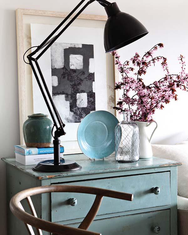 Cómoda pequeña con pintura desgastada y una lámpara estilo industrial