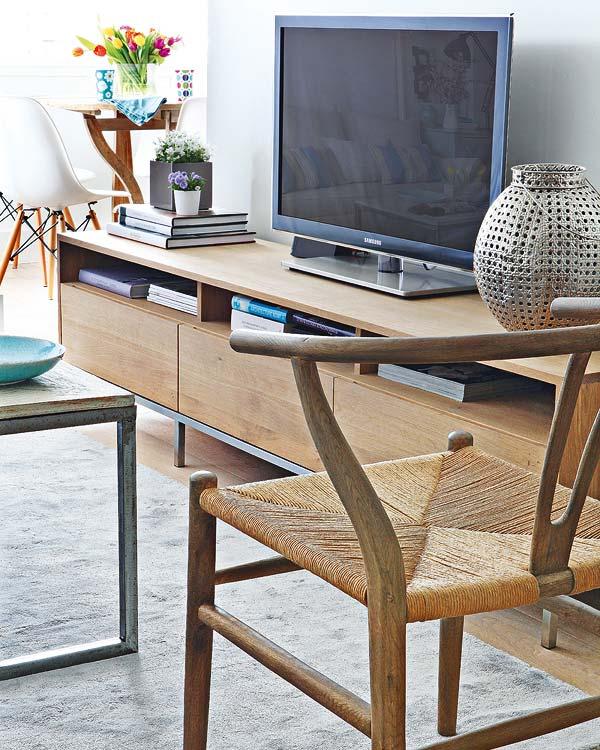 Mueble de TV contemporáneo apoyado sobre el tabique divisorio que oculta la cocina