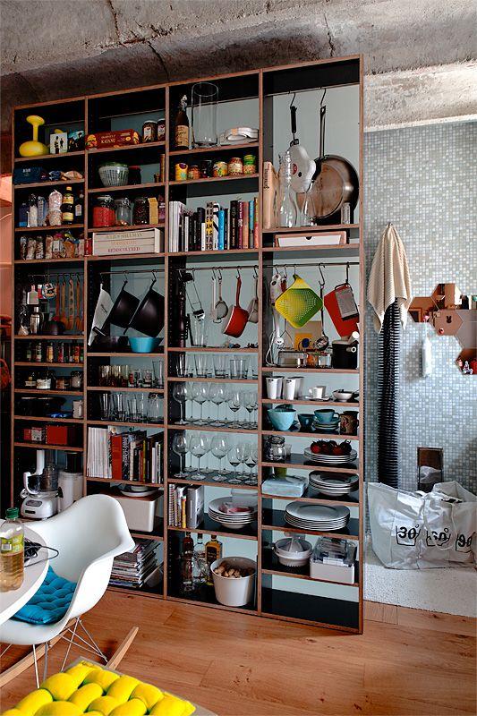 Espacio de guardado extra con una estantería en la cocina integrada del loft pequeño