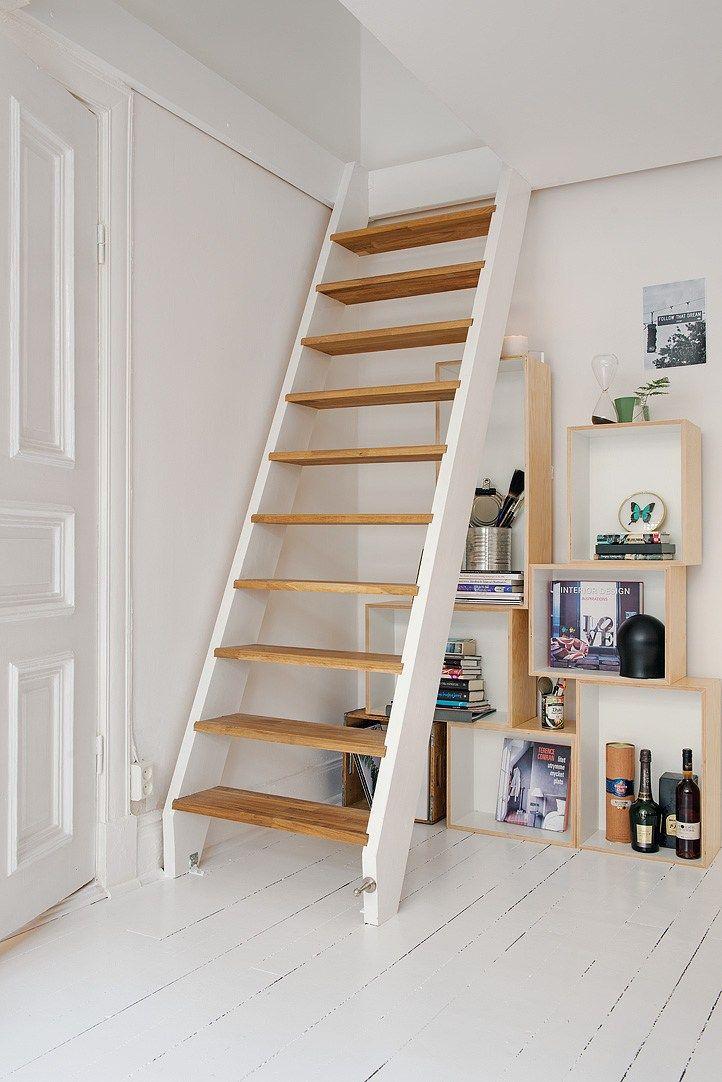 La escalera repite los colores de la decoración y se integra muy bien al resto del ambiente. Debajo, una biblioteca creada con cubos de madera suma espacio de guardado