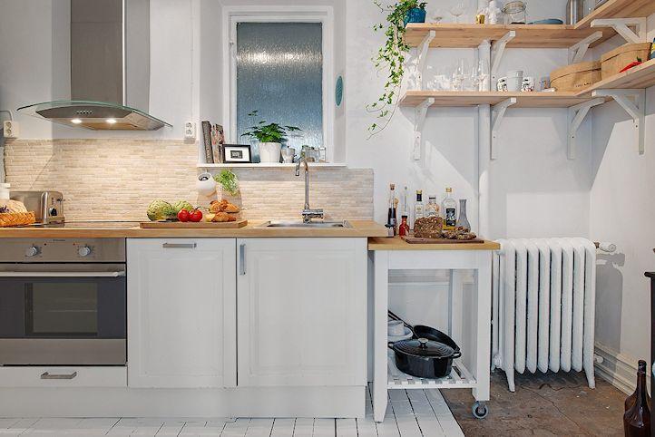 La cocina del monoambiente en estilo nórdico, con muebles blancos y mesada de madera.