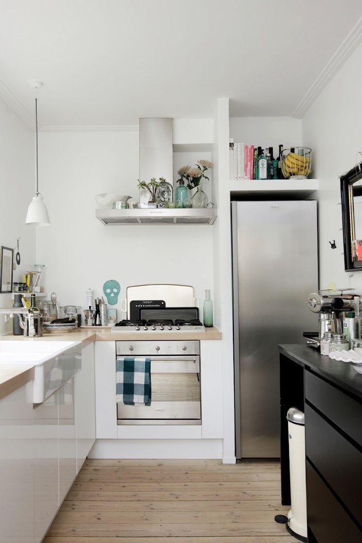 La cocina pequeña aprovecha muy bien el espacio con un diseño en L complementado con un mueble negro que la separa del ambiente principal
