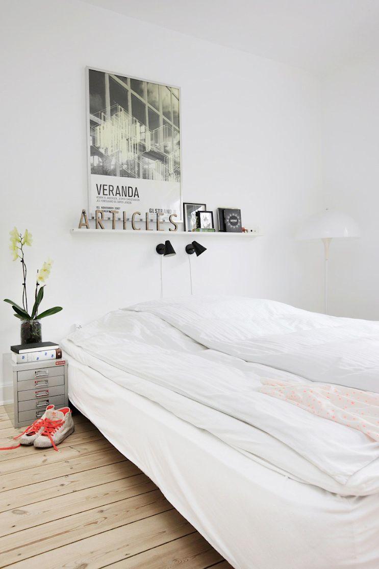 Dormitorio pequeño estilo nórdico con pocos muebles pero mucha decoración en las paredes