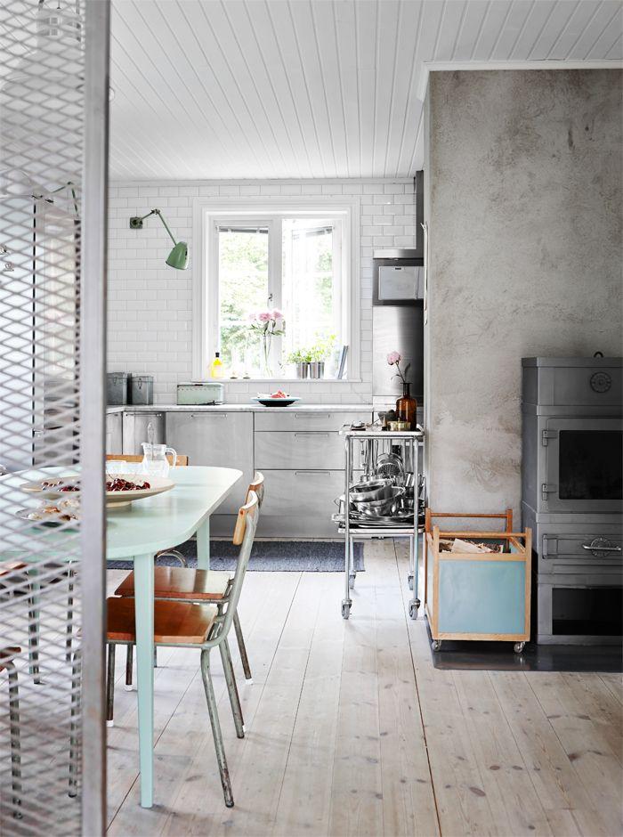 Paredes revestidas en cemento alisado, muebles en acero, cerámicos hasta el techo dan a la cocina un estilo industrial muy marcado
