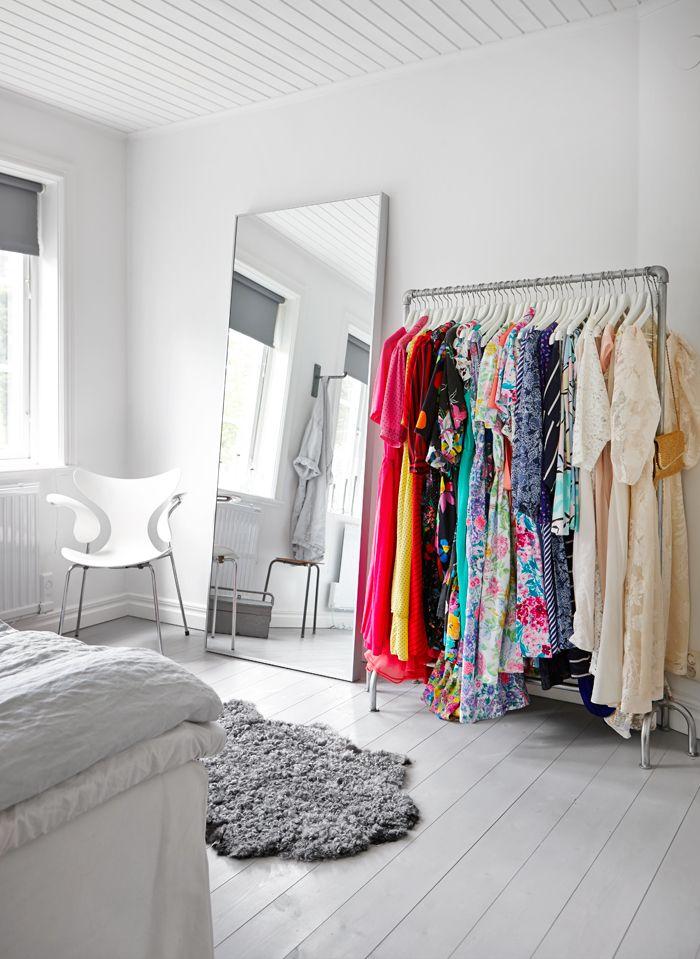 Perchero fabricado con tuberías metálicas suma espacio de guardado extra mientras que la ropa a la vista agrega color a la decoración