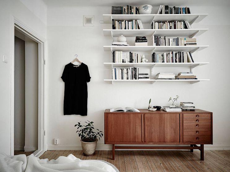 Un aparador suma espacio de guardado mientras que los estantes aprovechan el espacio vertical del monoambiente