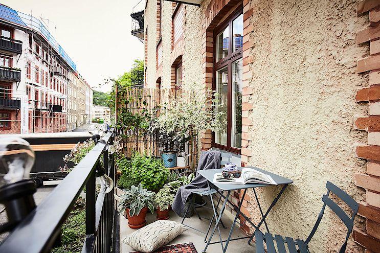 Diseño del balcón pequeño con plantas y un divisor de cañas para dar privacidad