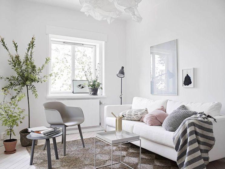 Monoambiente pequeño en estilo nórdico: living con sofá de Ikea blanco y pocos muebles