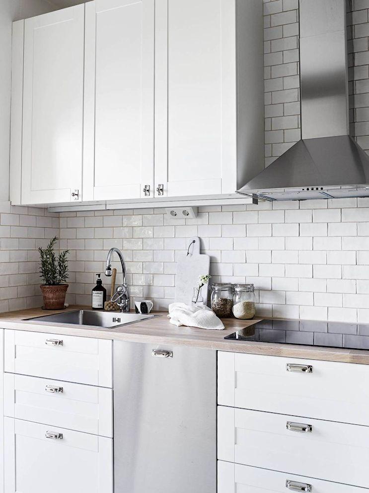 Cocina con cerámicas blancas colocadas al estilo subway, muebles blancos y mesadas de madera