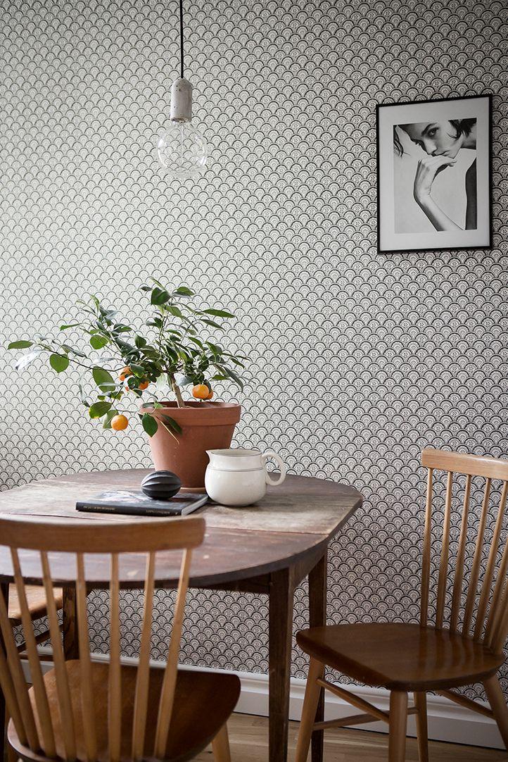 El empapelado en blanco y negro junto a las sillas y mesa de madera antigua dan un aire retro a la decoración de la cocina-comedor