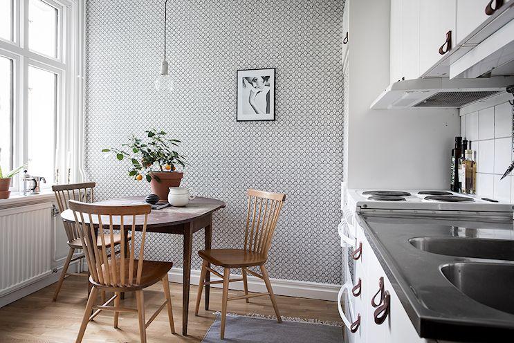 La cocina del monoambiente cuenta con lugar para una pequeña mesa de comedor y sillas, todos en madera