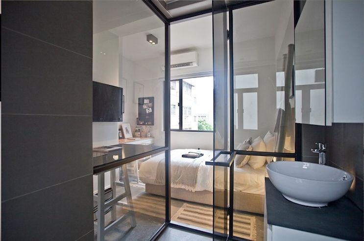 Baño integrado al ambiente principal con una pared vidriada
