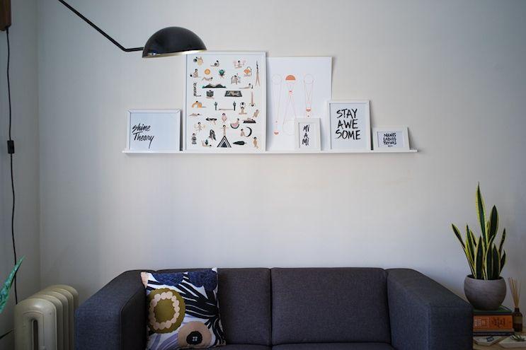 Monoambiente de 20 metros² en estilo moderno y en tonos neutrales: sector del living, con un sofá gris y cuadros y láminas sobre la pared para delimitar visulamente el sector