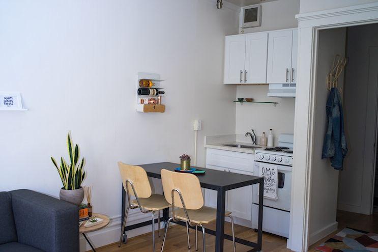 Monoambiente de 20 metros² en estilo moderno y en tonos neutrales: la mesa de comedor separa la kitchenette del resto del ambiente y suma espacio extra para preparar comidas