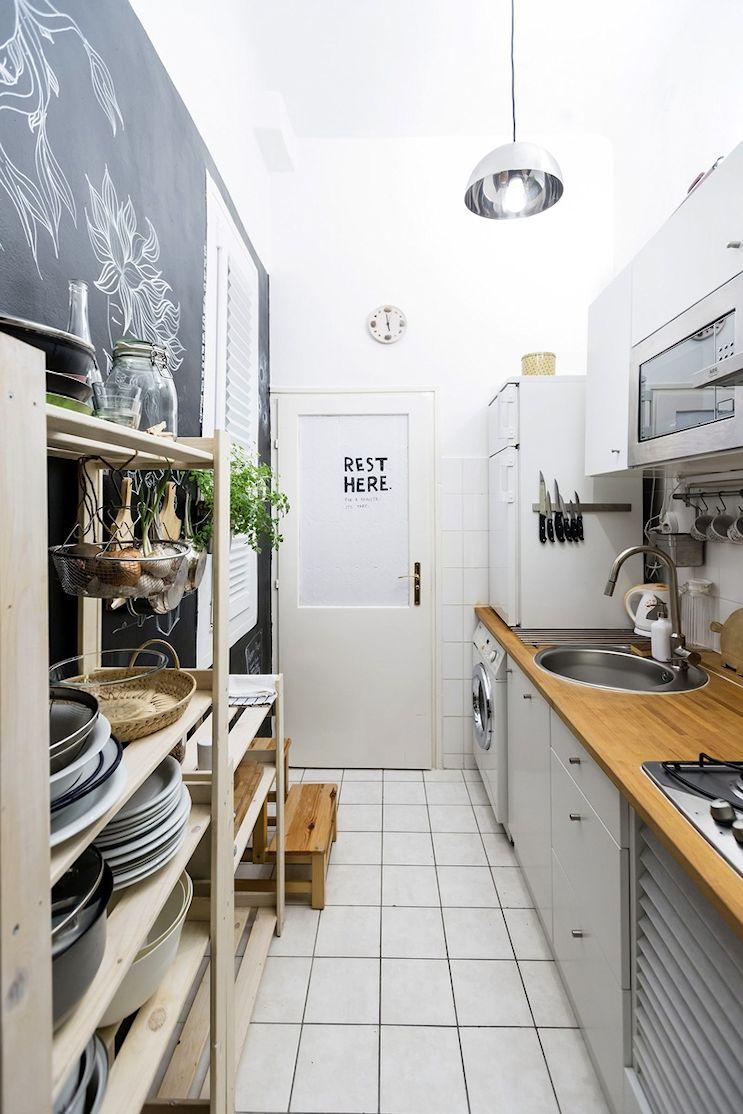 Cocina estilo nórdico con pared pintada con pintura de pizarra y mesadas de madera