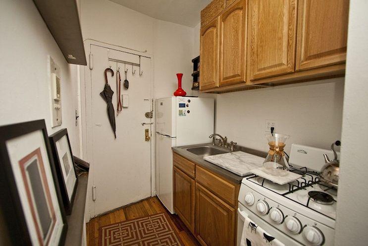 En la cocina se encuentra la puerta de acceso al monoambiente. Los cuadros y la alfombra rectangular hacen que el espacio se parezca más al ambiente principal.
