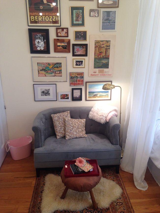 Sectorizar el área del living del monoambiente con una pared con cuadros y una pequeña alfombra