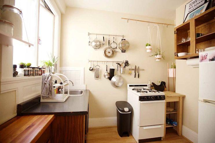 La cocina amplia que aprovecha el espacio vertical con alacenas y barras de acero inoxidable para colgar ollas, sartenes y utenisilios de cocina.