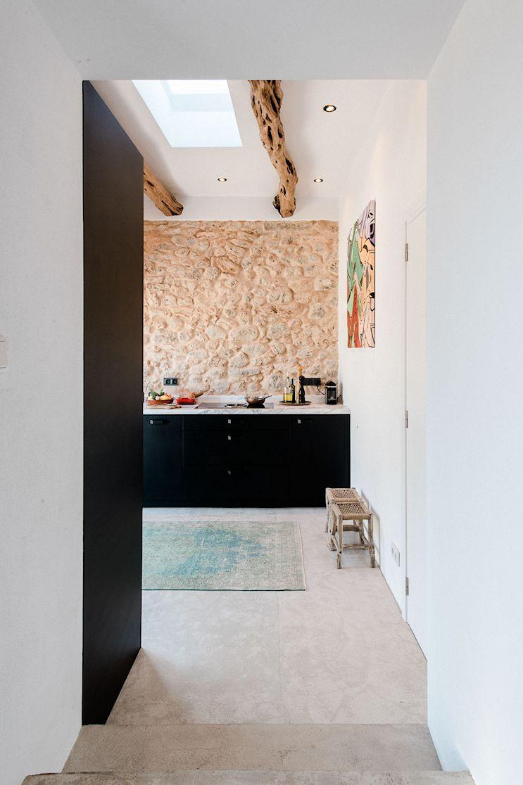 Cocina con paredes revestidas en piedra, pisos de cemento alisado y vigas en el techo de madera de Iroko