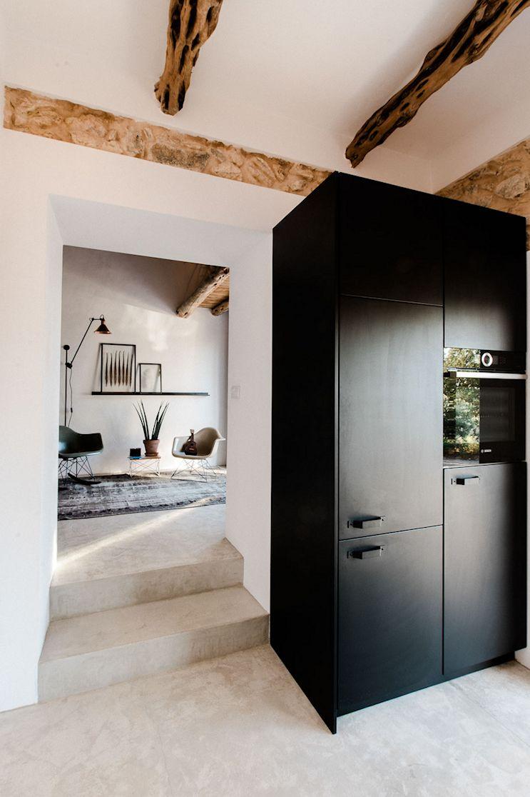 Los muebles de cocina en color negro contrastan con el resto de los elementos arquitectónicos