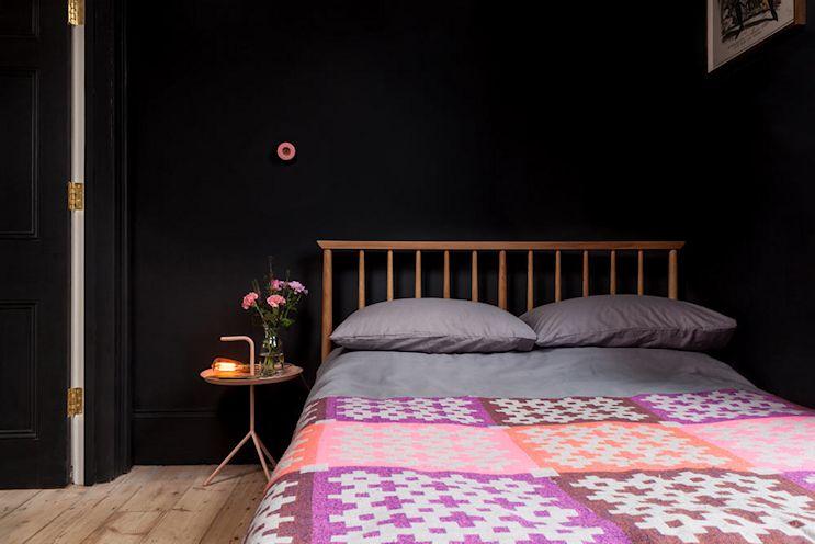 Las paredes y carpintería en negro logran un efecto envolvente e íntimo en el dormitorio