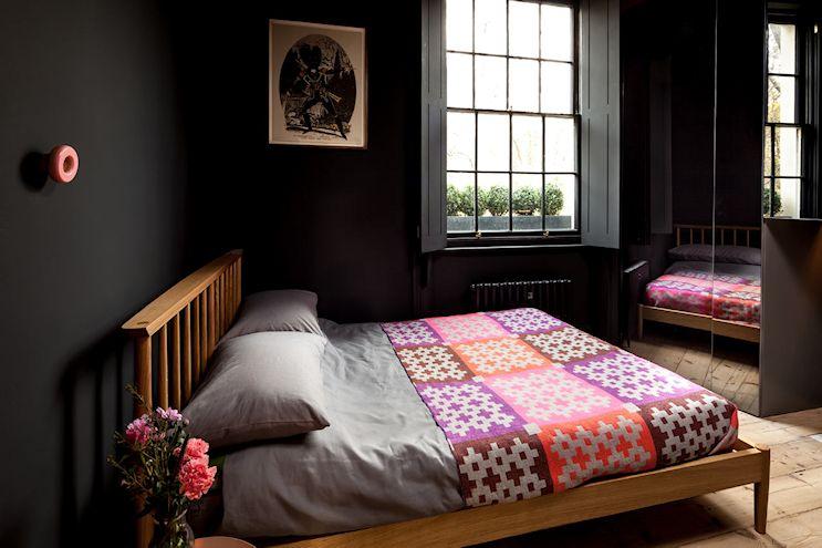 Pese a las paredes oscuras, el dormitorio sigue siendo un espacio luminoso