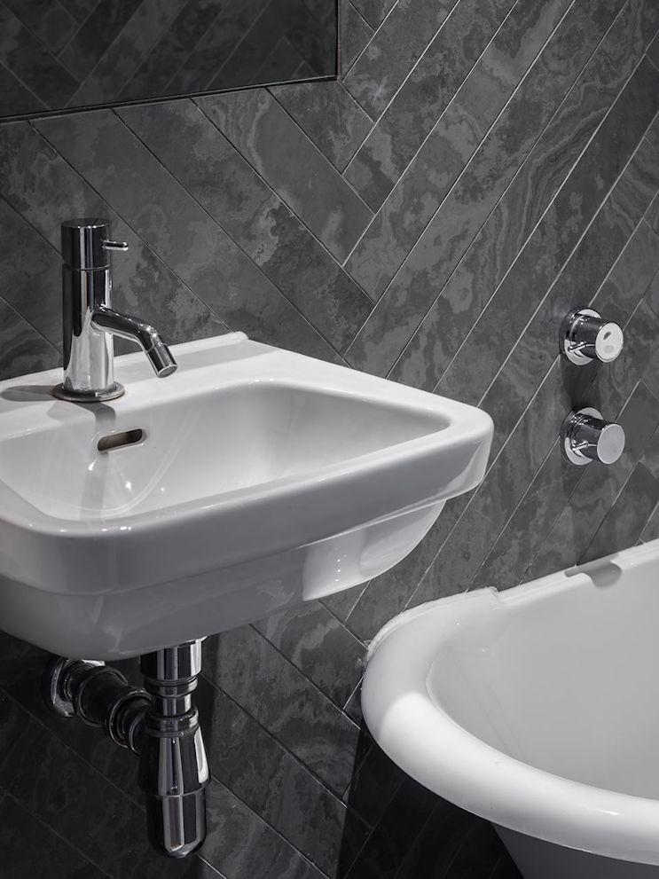 El revestimiento cerámico gris en paredes y pisos aporta elegancia y una estética clásica al baño