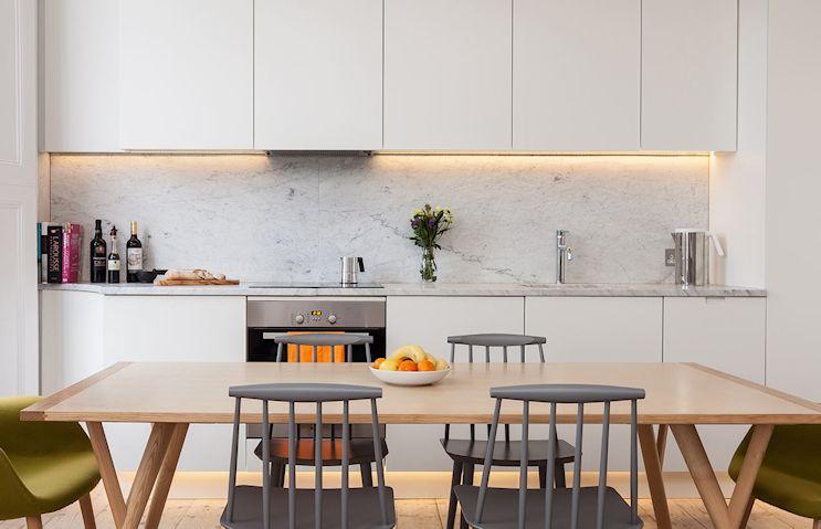 La cocina tiene un diseño linea aprovechando todo el ancho del ambiente. Repite la estética del living gracias a la mesada de mármol de carrara y la alzada en el mismo material
